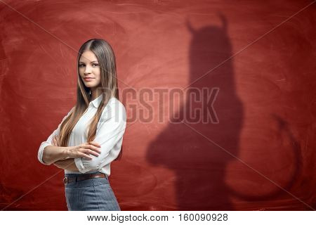 Young businesswoman is casting shadow of devil on rusty orange wall behind her. Unfair competition. Aggressive marketing strategies. Hidden motives.