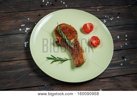 grilled beef steak and tomatoes garlic sauce on dark plate.