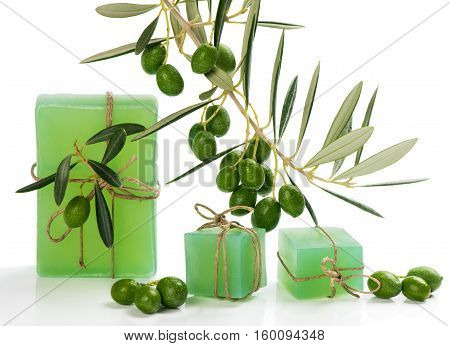 Olive soap and branch of olive tree with green olive fruits isolated on white background. Spa concept.