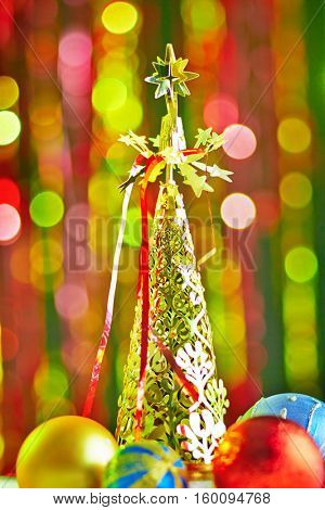 Decorative Christmas tree and Christmas balls on the blurred colored light background