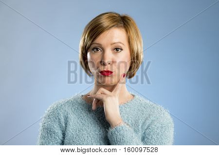 headshot portrait of young beautiful blond woman looking suspicious and grumpy in discontent and tension face expression isolated on blue background
