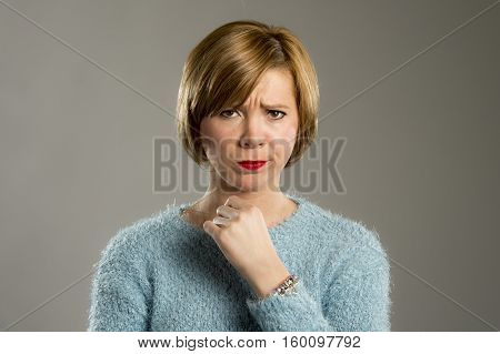 headshot portrait of young beautiful blond woman looking suspicious and grumpy in discontent and tension face expression isolated on grey background