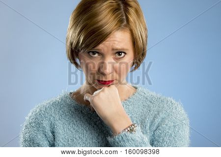 headshot portrait of young beautiful blond woman looking suspicious and sad in guilty and sorry face expression isolated on blue background