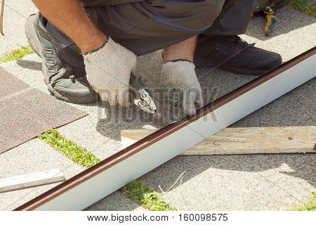 Roofer cuts profile on metal scissors close up