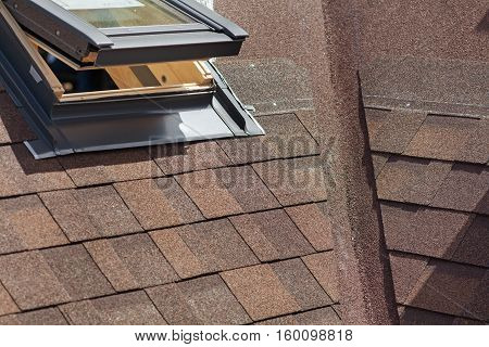 Closeup of window skylight on a roof with Asphalt Shingles or Bitumen Tiles under construction