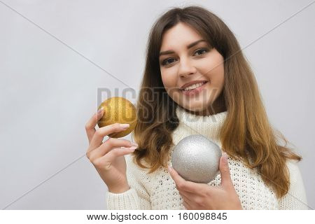 Portrait of a young girl in white sweater with christmas balls in hands, isolated on light grey background