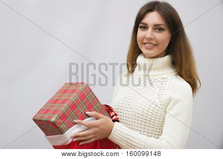 The girl is putting girt box in santa bag