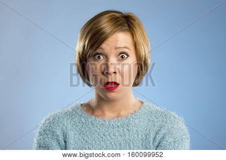 headshot portrait of young beautiful blond woman in surprise and shock face expression expressing anxiety and fear emotion with opened mouth isolated on blue background
