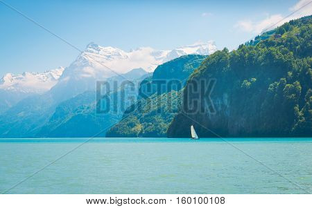 Grandiose mountain landscape. Mountain tops in the snow. White sail on a romantic lake.