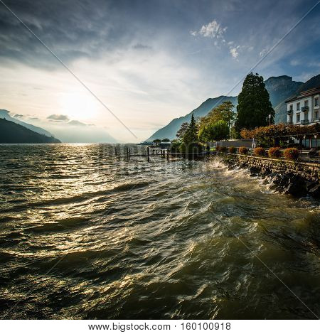 Storm and wind on the lake of Swiss Alps. Splash of waves in the setting sun. High Dynamic Range Image.
