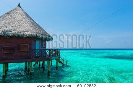 Bungalow with stair descending into the sea. Turquoise color of the lagoon. Tropical island in the Indian Ocean. Luxury holiday.