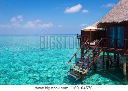 Turquoise lagoon in a tropical ocean over-water bungalow with steps into the water.