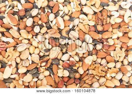 Background of mixed nuts: pistachios, peanuts, walnuts, almonds, hazelnuts, Brazil nuts, pumpkin seed and cashews mixed together