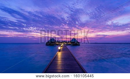 Gorgeous sunset over the ocean. Splash of waves on the white sand beach. Relaxing summer evening. Panorama of tropical island Beach with Overwater bungalows