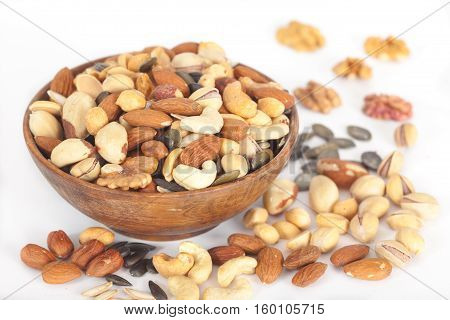 Mixed nuts: Pistachios, peanuts, walnuts, almonds, hazelnuts, Brazil nuts, pumpkin seed and cashews in wooden bowl
