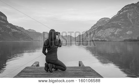 The female figure is sitting with a camera in hand on a wooden pier. Mountain landscape at sunset reflected in the lake. Black and white.