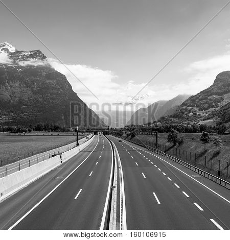 Empty highway is among the alpine mountains and fields. Path of Switzerland towards Italy St. Gotthard tunnel black and white