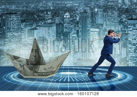 Businessman pulling boat made from dollar banknote
