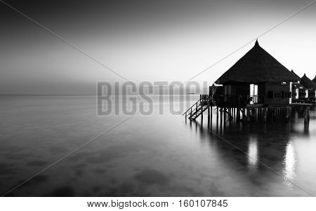 Panorama of tropical island resort with overwater bungalows at night in black and white. Ari Atoll.