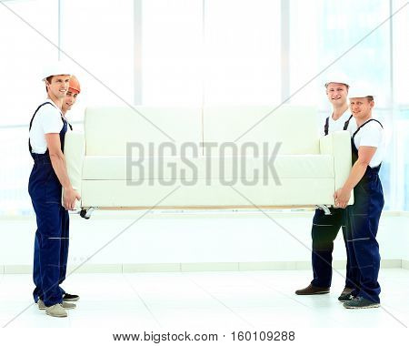 happy male movers in uniform carrying white sofa