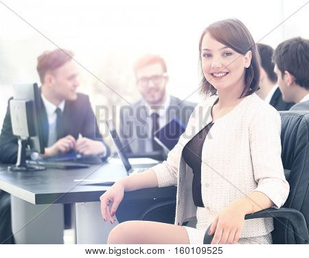 Portrait of a charismatic woman at a meeting while her team working in the background