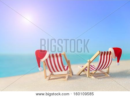Two striped red-white sunloungers with Christmas Santa hats for romantic couple at ocean sandy sunset beach New Year travel destinations concept for vacation in hot countries