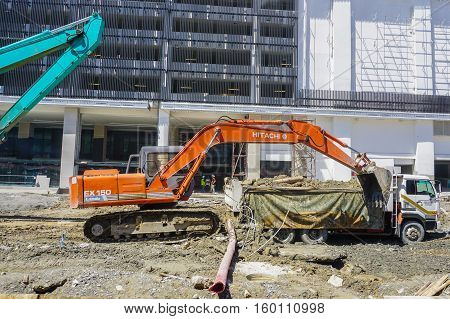 Kota Kinabalu,Sabah-Nov 28,2016:Building construction works with yellow excavator and lorry during sunny day.