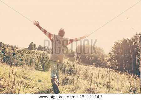 Boy running and raising his arms in the air, shallow focus