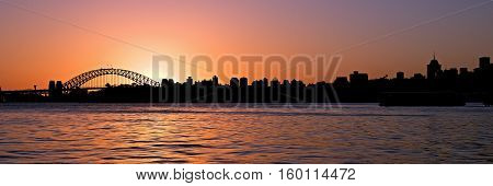 Sydney harbour bridge and North Sydney skyline CBD silouhette photo at sunset with pink/ orange/salmon glowing sky. New South Wales Australia.