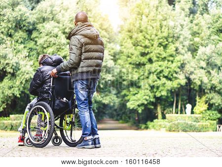 Back view of a carer man with young disabled with handicap on wheelchair outdoor in a park - Special needs care assistant working with disability - Social issues with invalid guy on difficulties