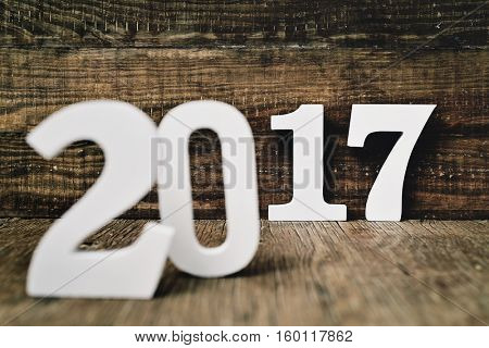 three-dimensional white numbers forming the number 2017, as the new year, on a rustic wooden surface