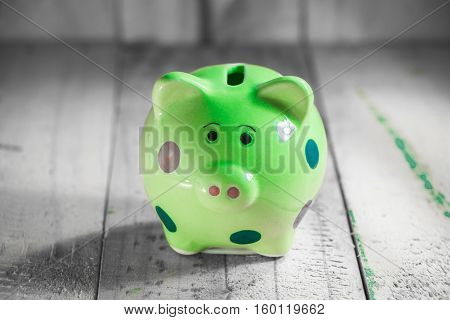 green piggy bank on wooden tabletop background