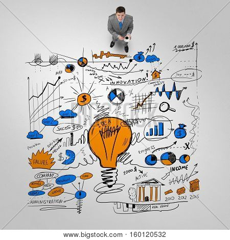 Top view of businessman with coffee cup and plan sketches on floor