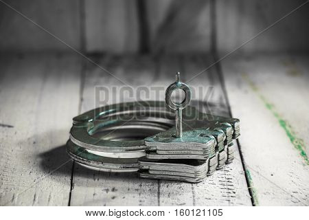 Handcuffs with key put on wooden table.
