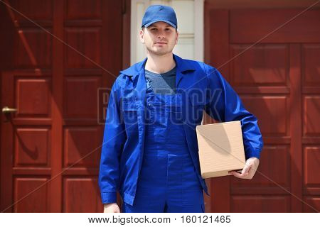 Young male deliverer with box in yard