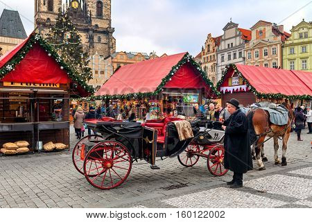 PRAGUE, CZECH REPUBLIC - DECEMBER 10, 2015: Carriage and wooden stalls on Old Town Square during traditional annual Christmas market taking place in december in Prague.