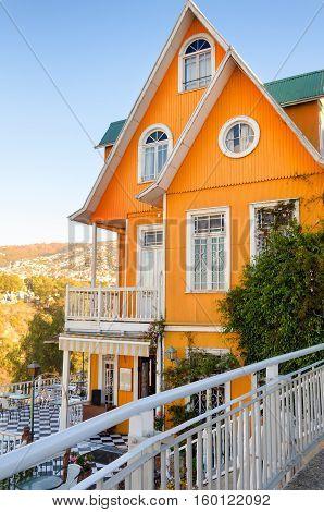 A flash of orange brightens a lofty hillside in Valparaiso Chile