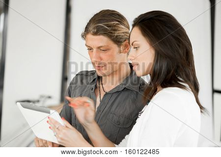 Young coworkers working together and discussing points while using tablet