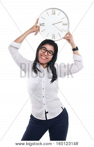 Photo image portrait of a happy and beautiful young Asian businesswoman smiling while showing time on clock with both hands holding the clock over her head half body close up portrait over white