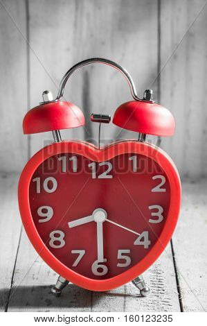 Red alarm bell on old wooden texture background mark at 8.30 o'clock