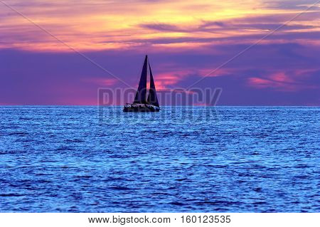 Sailboat sunset silhouette is a sailboat sailing along the water with a colorful night sky in the background.