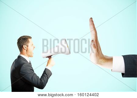 Irritated young man with megaphone screaming at hand showing stop gesture on blue background. Protest concept