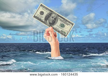 Hand with dollar bill sticking out of ocean. Sky background. Finance and risk concept