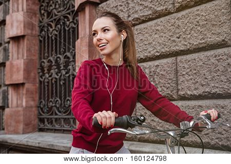 Photo of young woman dressed in sweater walking with her bicycle near wall on the street and smiling while listening music. Look aside.