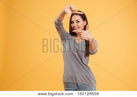 Pretty model in studio pretends to be photographed. isolated orange background