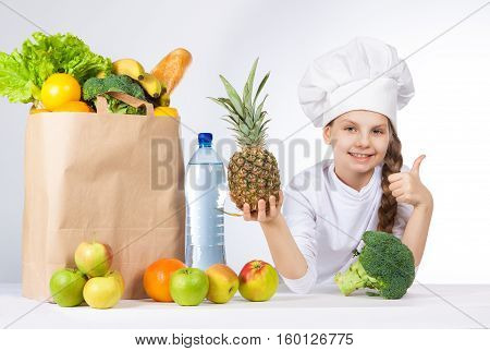 Little Happy Girl In A Cap Cook A Variety Of Fresh Food. Girl Holding Pineapple. And Shows Ok. Posit
