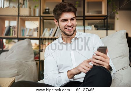 Happy businessman dressed in white shirt sitting in cafe and chatting by phone