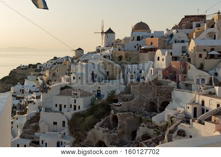 Sunset over white windmills in  town of Oia and panorama to Santorini island, Thira, Cyclades, Greece