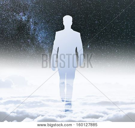 Back view of walking businessman silhouette on cloudy sky abd space background. Success concept