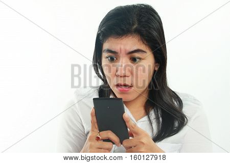Photo image portrait of a cute young Asian woman with mole looked shocked and sad to get bad news on her smart phone. Holding phone with both hands while reading message on it over white background